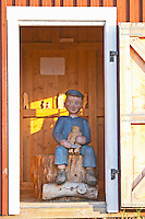 Astrid Lindgren's mischievous Emil sitting in the carpentry hut carving wood figurines as a penance. Lonneberga Smaland region. Sweden, Europe.