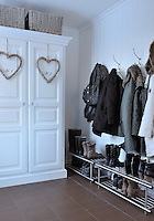 A cupboard in the entrance hall has been hung with festive woven hearts
