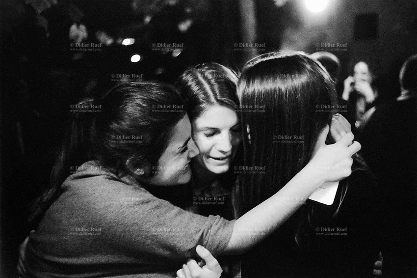 """Switzerland. Canton Ticino. Oggio. Grotthard Café. Micaela Ruef (L), Camille de Righetti (C) and Paola Ranghino (R) celebrate their Matura with joy and emotion. They gently hug together and let themselves be happy. Matura or its translated terms (Mature, Matur, Maturita, Maturità, Maturität,) is a Latin name for the high-school exit exam or """"maturity diploma"""". It is taken by young adults (usually aged from 17 to 20) at the end of their secondary education, and generally must be passed in order to apply to a university or other institutions of higher education. Matura is a matriculation examination and can be compared to A-Level exams or Abitur. A hug is a form of physical intimacy, universal in human communities, in which two people put their arms around the neck, back, or waist of one another and hold each other closely. If more than two persons are involved, this is informally referred to as a group hug. 28.06.15 © 2015 Didier Ruef"""