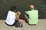 Woman and man discussing life while sitting along stream. Boulder, Colorado. .  John offers private photo tours in Denver, Boulder and throughout Colorado. Year-round Colorado photo tours.