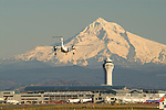 Portland International Airport with a plane landing and snow-covered Mt. Hood in the background.