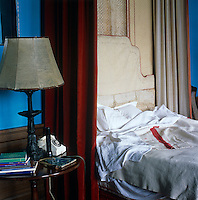 A four-poster bed with velvet hangings and a bare headboard has antique linen sheets