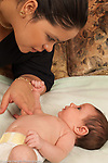 Newborn baby girl, 1 month old, with mother looking at her and listening to her