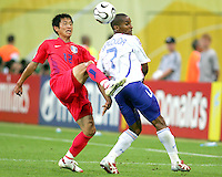 Young Pyo Lee (12) of Korea hooks the ball behind Florent Malouda (7) of France. The Korea Republic and France played to a 1-1 tie in their FIFA World Cup Group G match at the Zentralstadion, Leipzig, Germany, June 18, 2006.