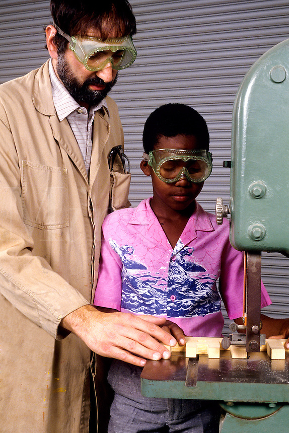 Teacher helping black african american student in grade 6 with industrail shop class in schoo