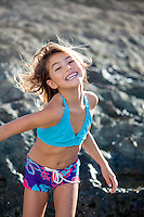 A happy young girl plays at a rocky North Shore beach on O'ahu.