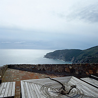Driftwood provides a centrepiece for the outdoor dining table on this roof terrace overlooking the sea