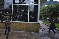 BOGOTÁ - COLOMBIA, 27-09-2019:En una asonada con bombas Molotov y piedras  por parte de encapuchados contra el edificio del ICETEX  termino la  marcha de los estudiantes de las universidades públicas y privadas en protesta por la corrupción administrativa y los excesos del ESMAD de la Policia Nacional./In an assault with Molotov bombs and hooded stones against the ICETEX building, the march of students from public and private universities ended in protest against administrative corruption and the excesses of the National Police ESMAD. Photo: VizzorImage / Diego Cuevas / Contribuidor