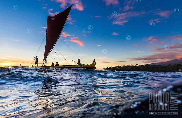 Visitors take in the sunset and a cultural tour on one of Keauhou Bay Adventures' Hawaiian canoes, Big Island of Hawai'i.