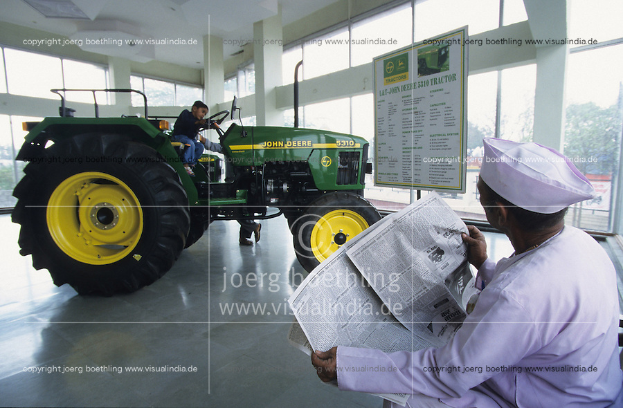 INDIEN Maharashtra, Bauer mit Zeitung bei einem Traktor Haendler von John Deere und Larssen&Toubro L&T Joint venture  -  INDIA farmer with newspaper at John Deere tractor dealer in Maharashtra, the tractors are produced in JD factory Pune/India