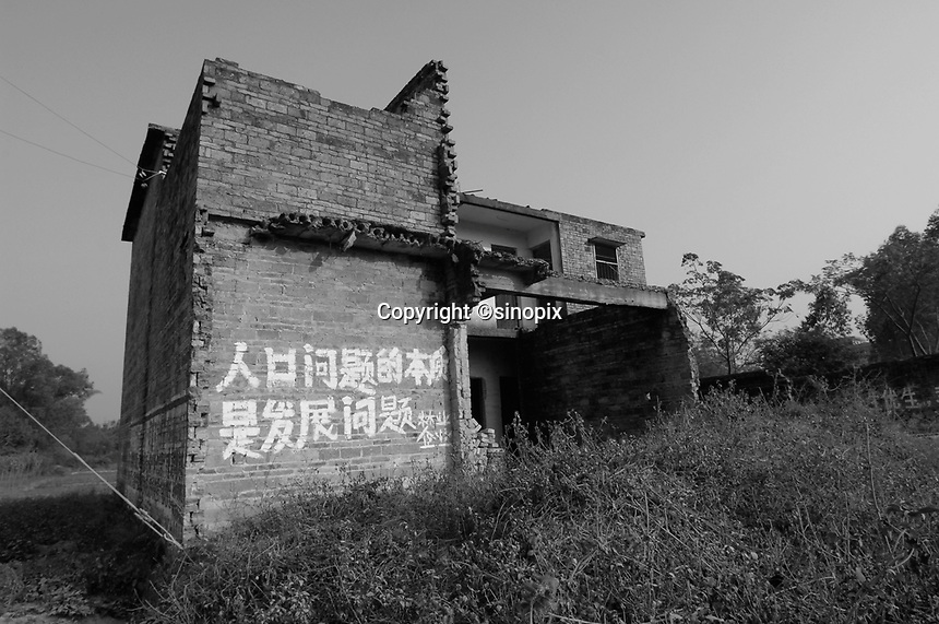 """A house in Bobai county outside Yingqiao that has been smashed up. The house and the surrounding area have slogans from the One Child Policy, """"fewer babies better life"""" and """" a sensible birth policy is essential for development""""."""