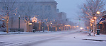 Idaho,Coeur d'Alene. Sherman avenue with lighted trees in falling snow at dawn.