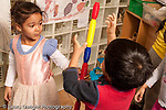Preschool Headstart 3-5 year olds girl in dressup costume building tower from colorful plastic tubes working with boy  horizontal