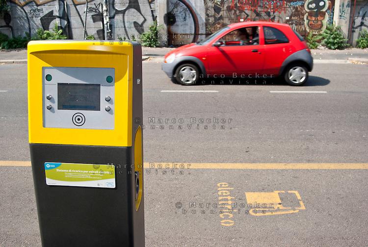 Milano, quartiere Bovisa, periferia nord. Una vettura a benzina e una postazione con colonnina per la carica di veicoli elettrici --- Milan, Bovisa district, north periphery. A petrol car and a parking for charging electrical vehicles