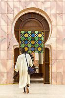 Senegal, Touba.  Man Entering the Grand Mosque, Shoes in Hand.
