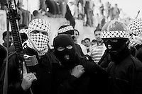 Members of the al-Aqsa Martyrs' Brigades walking outside the walls of the Muqata presidential compound the day of Yasser Arafat's funeral.