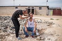 Fluechtlingscamp Arin Mirxan nahe der Ortschaft Suruc im tuerkischen Grenzgebiet zu Syrien. Hier leben ca. 250 Menschen, die vor dem Krieg des IS gegen die Kurden in dem Kurdengebiet Rojava von Syrien aus in die Tuerkei geflohen sind.<br /> Im Bild: Alltag im Fluechtlingslager, ein Mann bekommt den Bart von einem Mitfluechtling rasiert.<br /> 12.10.2015, Suruc/Tuerkei<br /> Copyright: Christian-Ditsch.de<br /> [Inhaltsveraendernde Manipulation des Fotos nur nach ausdruecklicher Genehmigung des Fotografen. Vereinbarungen ueber Abtretung von Persoenlichkeitsrechten/Model Release der abgebildeten Person/Personen liegen nicht vor. NO MODEL RELEASE! Nur fuer Redaktionelle Zwecke. Don't publish without copyright Christian-Ditsch.de, Veroeffentlichung nur mit Fotografennennung, sowie gegen Honorar, MwSt. und Beleg. Konto: I N G - D i B a, IBAN DE58500105175400192269, BIC INGDDEFFXXX, Kontakt: post@christian-ditsch.de<br /> Bei der Bearbeitung der Dateiinformationen darf die Urheberkennzeichnung in den EXIF- und  IPTC-Daten nicht entfernt werden, diese sind in digitalen Medien nach §95c UrhG rechtlich geschuetzt. Der Urhebervermerk wird gemaess §13 UrhG verlangt.]