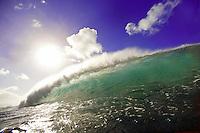 clean blue/green water reflects the sun as wave breaks under blue sky