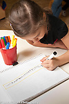 Education Preschool 4-5 year olds girl using left hand to write column of numbers