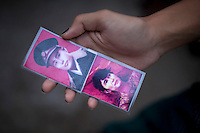 A National League of Democracy supporter holds a laminated card of General Aung (left) and his daughters Aung San Suu Kyi (right) outside her party headquarters the day after her release from house arrest in Rangoon. From 1990 until her release on 13 November 2010, Aung San Suu Kyi had spent almost 15 of the 21 years under house arrest.