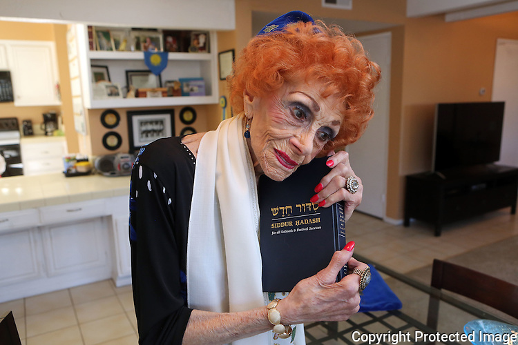 Lillian Wasserman wearing her prayer shawl, and yarmulke and holdiing a book of scripture she has been studying at her La Costa home. photo by Bill Wechter