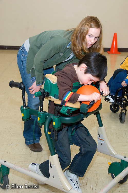 MR / Albany, NY.Langan School at Center for Disability Services .Ungraded private school which serves individuals with multiple disabilities.Teacher's aide moves child in a gait trainer as he grasps the ball to try to tag someone out during a modified Adaptive Physical Education class (APE) game of T-ball.  Boy: 8, cerebral palsy, spastic quadriplegic, nonverbal with expressive and receptive language delays.MR: Neu1; Hac2.© Ellen B. Senisi