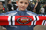 FC United of Manchester 8, Glossop North End 0, 28/10/2006. Gigg Lane, Bury, North West Counties League division one. A young fan of FC United of Manchester holding up a scarvf in his team's colours before they take on Glossop North End (blue shirts) in a North West Counties division one match at United's home stadium, Gigg Lane, home to Bury FC. The match was staged on People United Day, an event started in 1999 which brought together fans from across Europe to campaign against racism. FC United were formed in the summer of 2005 by supporters of Manchester United in response to the take over of their club by American millionaire Malcolm Glazer and his family. The club entered the football pyramid at the lowest level with the intention to climbing through the leagues. FCUM won the match 8-0, watched by 3257 spectators. Photo by Colin McPherson.