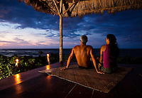 A couple watches the sunset from their beachfront gazebo