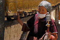 Tibetan Buddhist with prayer wheel and mala beads circumambulates rows of prayer wheels on the Barkhor pilgrim circuit around the Jokhang Temple, Lhasa, Tibet.