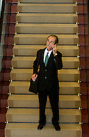A man pauses on a staircase while talking on a mobile phone. Model is model released.