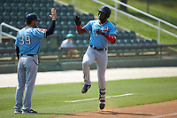 Sherten Apostel (13) of the Hickory Crawdads high fives Hickory Crawdads manager Matt Hagan (39) as he rounds the bases after hitting a solo home run against the Kannapolis Intimidators at Kannapolis Intimidators Stadium on June 2, 2019 in Kannapolis, North Carolina. The Intimidators defeated the Crawdads 4-3. (Brian Westerholt/Four Seam Images)