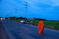 A Buddhist Monk crossing the rural highway at twilight near Battambang, Cambodia