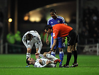 Pictured: Leon Britton of Swansea on the ground is being spoken to by match referee A Marriner (R), after being tackled by Florent Malouda of Chelsea (C). Tuesday, 31 January 2012<br /> Re: Premier League football Swansea City FC v Chelsea FCl at the Liberty Stadium, south Wales.