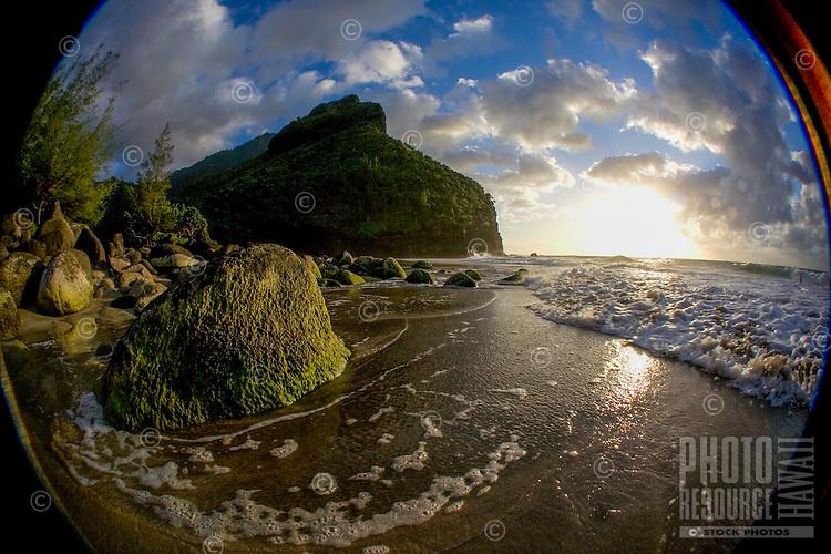 The setting sun is reflected on waves rushing onto shore at Hanakapi'ai Beach, Na Pali Coast, Kaua'i.