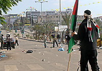 """Palestinian supporters of the secular Fatah movement throw stones at Hamas policmen during clashes at a huge gathering in Gaza city, 12 November 2007. Gunfire erupted killing at least five demonstrators and wounding at least 10 in Gaza City today as hundreds of thousands gathered to mark the death of Yasser Arafat in the biggest rally organised by the Fatah party since its ouster by Hamas. Shots rang out after the crowds started chanting """"Shiite, Shiite"""" -- accusing the Islamist movement of being a proxy for Shiite Iran and its ally Syria, witnesses and medics said. .""""photo by Fad Adwan"""""""