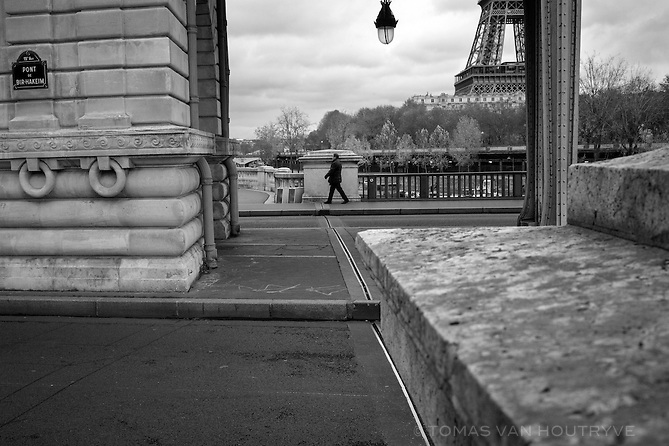 A pedestrian walks across the Pont de Bir Hakeim bridge in Paris, France, four days after coordinated terrorist attacks struck the heart of the French capital. Seen in the background, the Eiffel Tower was closed to visitors again after briefly opening Monday.
