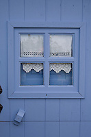 A detail of a blue painted wooden door with a white lace curtain behind a small square window