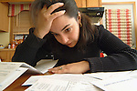 young adult woman sitting at kitchen table holding head and stressed by pile of unpaid bills.