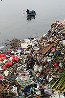 An Indonesian fisherman paddles past a large pile of trash in the port area of Jakarta.<br /> <br /> To license this image, please contact the National Geographic Creative Collection:<br /> <br /> Image ID:  1588017<br />  <br /> Email: natgeocreative@ngs.org<br /> <br /> Telephone: 202 857 7537 / Toll Free 800 434 2244<br /> <br /> National Geographic Creative<br /> 1145 17th St NW, Washington DC 20036