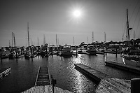 Boats are moored while the afternoon sun beams down.  Converted to black and white.