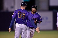 Fort Myers Mighty Mussels manager Brian Meyer (16) low fives Jeferson Morales (5) as he rounds third on a home run by Charles Mack (not shown) during a game against the Tampa Tarpons on May 20, 2021 at George M. Steinbrenner Field in Tampa, Florida.  (Mike Janes/Four Seam Images)