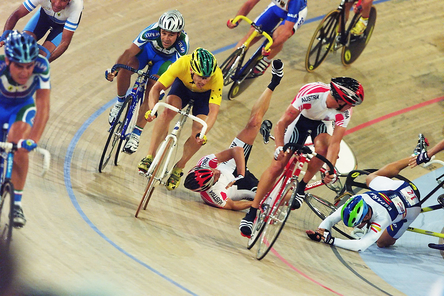 Australian rider Brett Aitkin threads his way through a dramatic crash in the closing laps of the Madison race to take the gold medal at the Sydney Olympic Games.