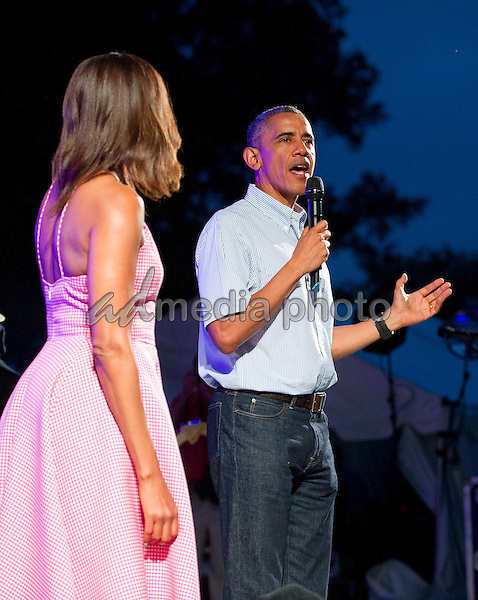 United States President Barack Obama, accompanied by first lady Michelle Obama, arrives to make remarks to members of the military and White House staff who were invited to the South Lawn of the White House in Washington, D.C. on Saturday, July 4, 2015.  The guests were treated to a Bruno Mars concert and the traditional fireworks on the National Mall.  An earlier Bar-B-Que had been planned but was cancelled due to inclement weather. Photo Credit: Ron Sachs/CNP/AdMedia