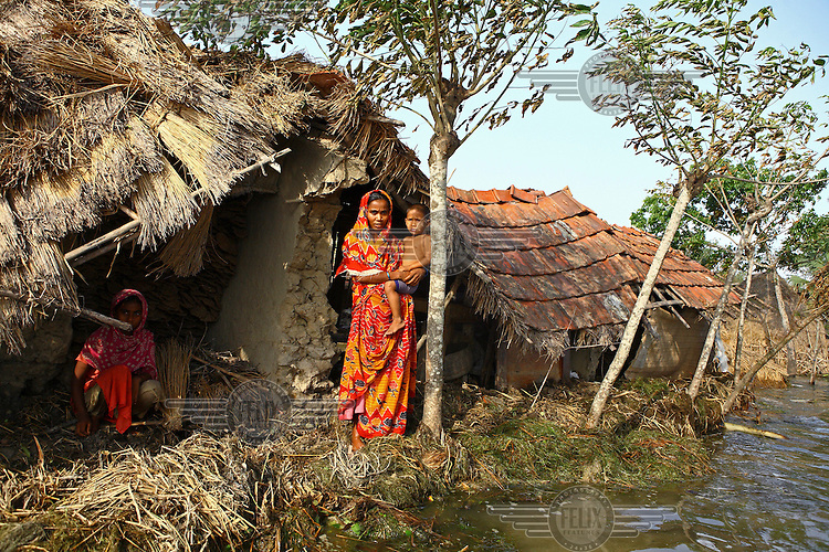 A mother and child stand outside their partially submerged home. Thousands of people were displaced in Shyamnagar Upazila, Satkhira district after Cyclone Aila struck Bangladesh on 25/05/2009, triggering tidal surges and floods..