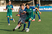 HARTFORD, CT - JULY 10: Thomas Janjigian #20 of Hartford Athletic dribbles as Austin Brummett #71 of New York Red Bulls II defends during a game between New York Red Bulls II and Hartford Athletics at Dillon Stadium on July 10, 2021 in Hartford, Connecticut.