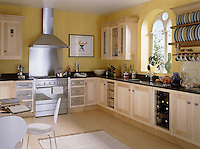 A modern ktichen with light wood units. A stainless steel cooker hood is placed above a range oven and the room has a breakfast table and chairs.