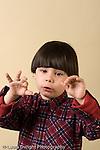 preschool boy singing and making hand gestures vertical closeup