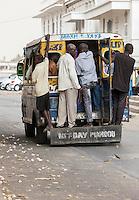Senegal, Saint Louis.  Men Hanging on to the Rear of a Minibus.
