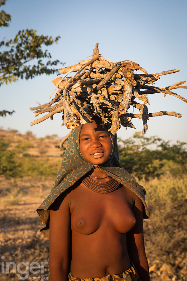 A Himba Girl carrying fire wood at sunset in remote Kaokoland, Namibia