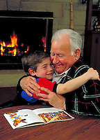 Boy and grandfather hug as they express love at home near the fireplace. Grandfather and grandson.